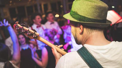 Eine Band spielt auf einer Bühne. Davor steht das Publikum, klatscht und tanzt.