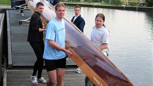 Studierende tragen ein Ruderboot zum Steg