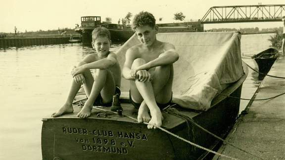 Zwei Jungen sitzen auf einem Boot des Ruderclub Hansa in den 1960er Jahren.