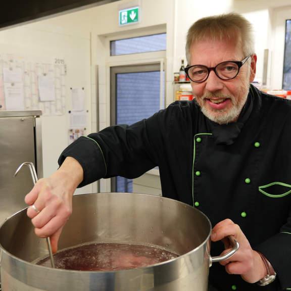 Hansa Gastronom Peter Barkholtz rührt mit einer Kelle in einem sehr großen Topf