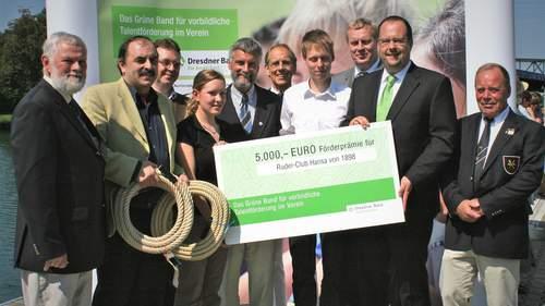 Bei der Auszeichnung mit dem grünen Band wird ein symbolischer Scheck übergeben. Eine Gruppe von Menschen hält den Scheck und schaut in die Kamera.