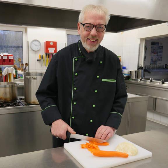 Hansa Gastronom Peter Barkholtz schneidet Möhren mit einem Messer